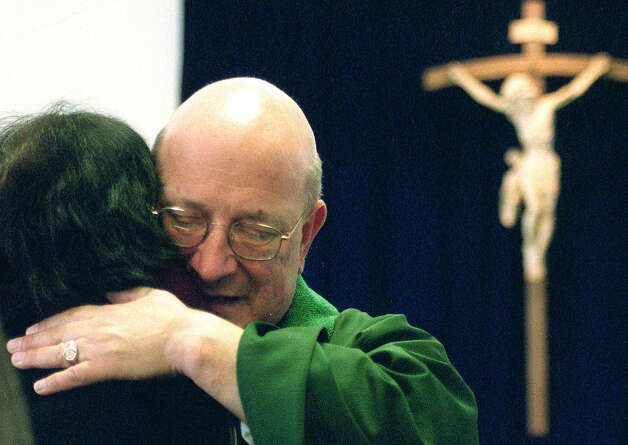 Beloved Father Tom Ptaszynski and parishioner hug during his farewell get-together at Our Lady of the Lakes in New Milford on Jan. 20, 2002 Photo: Norm Cummings, Norm Cummings/Spectrum / The News-Times