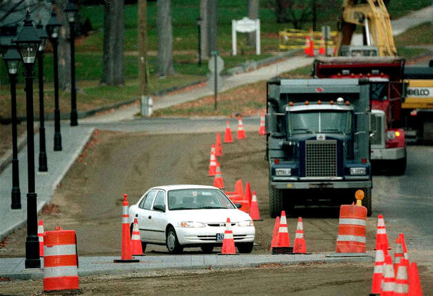 A car navigates through construction to build the downtown/skirting curb near Cramer & Anderson in New Milford. Photo: Norm Cummings/Spectrum
