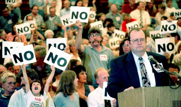 Originally a proponent of the Sempra power plant project, New Miford Mayor Art Peitler enjoys the support of numerous residents wielding 'no' signs as he offers his opposition to the proposal during a state Siting Council hearing at New Milford High School in 1999. Photo: Norm Cummings/Spectrum