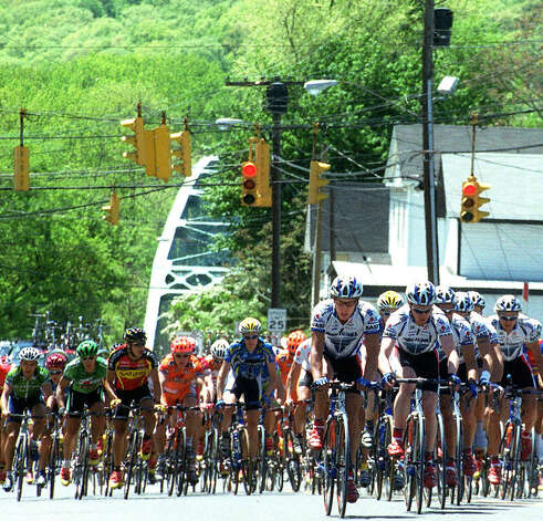 The pack of the third annual but short-lived Housatonic Valley Classic bicycle race speeds along Bridge Street inn New Milford on May 18, 2003. Photo: Norm Cummings, Norm Cummings/Spectrum / The News-Times