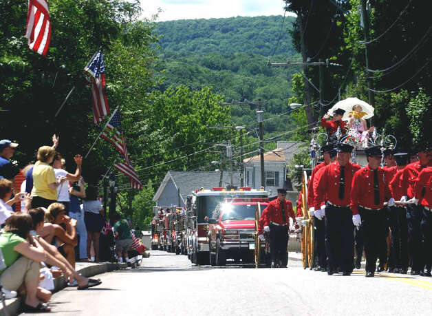 The Water Witch Hose Co. No. 2 firefighters, with kids aboard their iconic carriage, march along Bennitt Street during the July 1, 2007 tricentennial parade in New Milford Photo: Walter Kidd