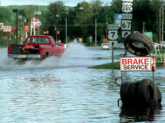 'Brake service' might well come in handy for the many motorists who attempt to drive through Route 7 floodwaters in New Milford, such as this adventurous soul following Hurrican Floyd in September of 2000. Photo: Norm Cummings/Spectrum