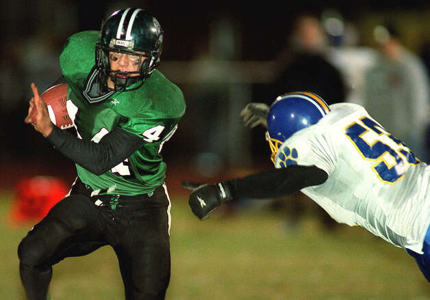 New Milford High School football's Vin Pullicino runs for a touchdown in the second quarter as  Brookfield linebacker Dave Eggleston tries to stop him on Oct. 26, 2001   Spectrum file photo Photo: Tim Wheeler/Spectrum / The News-Times Contributed