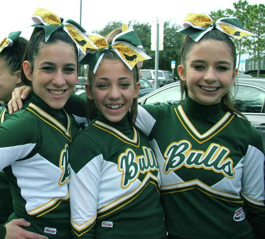 Relaxed and confident as they head with their teammates to national competition are New Milford Bulls' Pop Warner Junior Midget cheerleaders, from left to right, Hannah Seigel, Olivia Thalissinos and Emily McGuire. The New Milford girls rose to the occasion in early December to claim national honors for their division.  Courtesy of the New Milford Bulls Photo: Contributed Photo