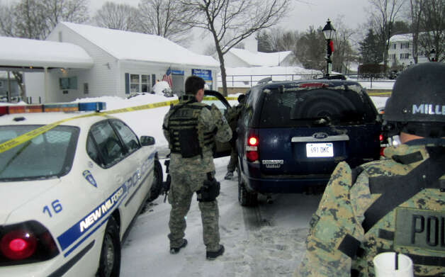 The streets and sidewalks around the drive-in branch of Webster Bank on the Village Green in New Milford were patrolled by heavily armed police from the Regional Emergency Response Group on Jan. 18, 2011 after a reported armed robbery at the bank. Police investigators were searching the downtown and throughout the area for a suspect. Photo: Norm Cummings