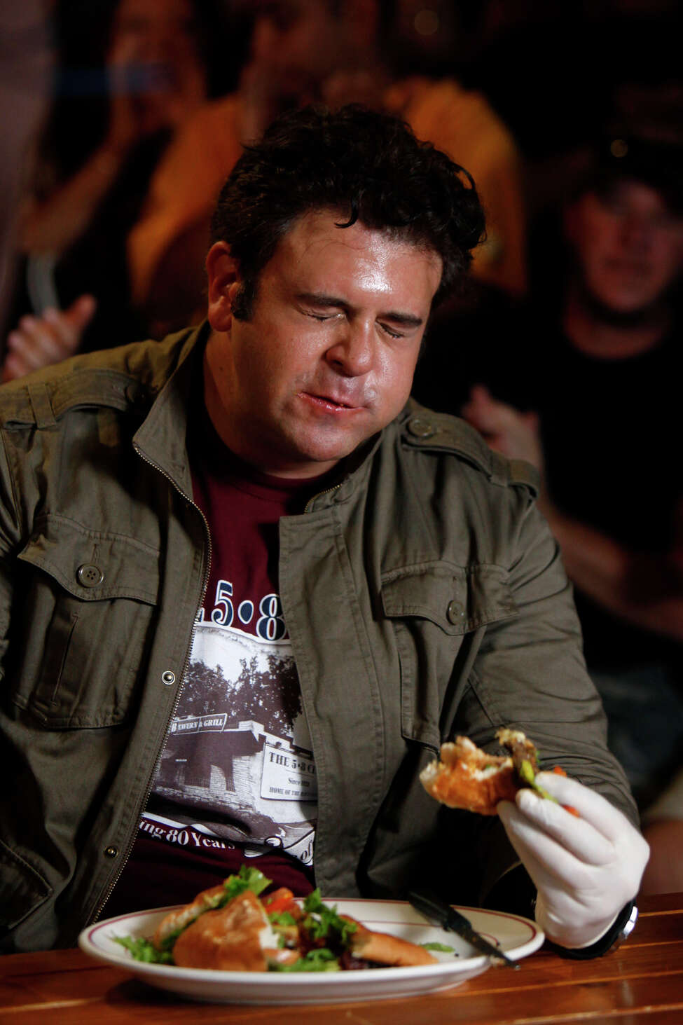 Adam Richman, host of the Travel Channel's 'Man vs. Food,' eats The Four Horseman burger during taping of the show at Chunky's Burgers and More in San Antonio on June 3, 2009.