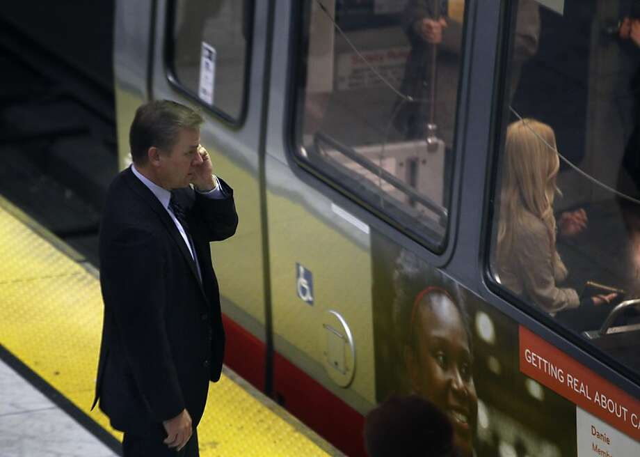 In this file photo, a passenger talks on his cell phone while waiting for a Muni Metro train. Train service was disrupted this morning after an equipment problem caused a power outage. Photo: Paul Chinn, The Chronicle