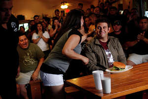 Waitress Sherry Avila delivers The Four Horseman to Adam Richman, right, host of the Travel Channel's 'Man vs. Food,' during taping of the show at Chunky's Burgers and More in San Antonio on June 3, 2009.