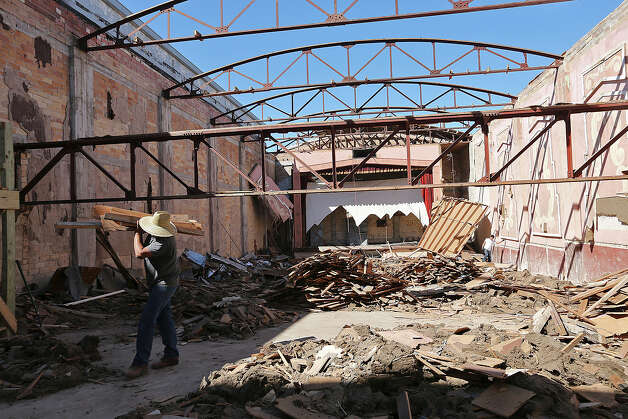 Workers remove debris from the former Rialto Theater in Kenedy, Texas, Thursday, Feb. 14, 2013. Houston developer Walter Chance bought the theater and the building next to it and is turning them into office and living spaces. Photo: Jerry Lara, San Antonio Express-News / © 2013 San Antonio Express-News