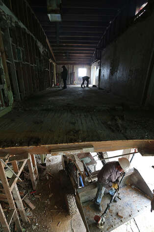 Workers gut the old Rialto Theater in Kenedy. Houston developer Walter Chance bought the theater and the building next to it and is turning them into office and living spaces. Photo: Jerry Lara, San Antonio Express-News / ©2013 San Antonio Express-News