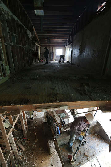 Workers gut the former Rialto Theater in Kenedy, Texas, Thursday, Feb. 14, 2013. With demand from co