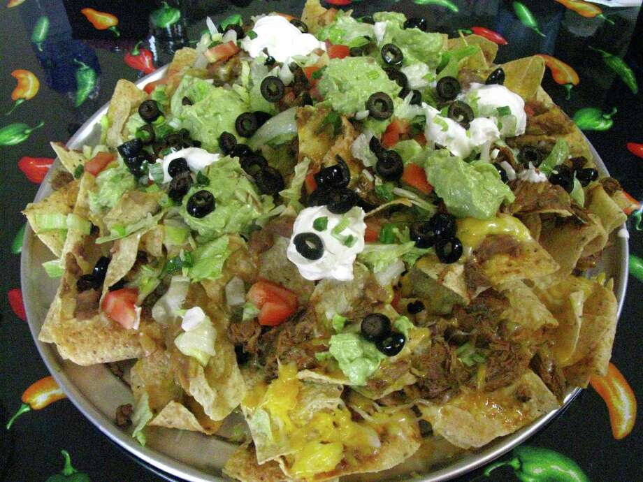 Extreme Nachos at Marianito's Extreme Tex-Mex Grill are served on a 16-inch pizza pan. Photo: JENNIFER MCINNIS, SAN ANTONIO EXPRESS-NEWS / JMCINNIS@EXPRESS-NEWS.NET