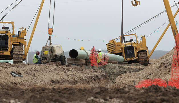 Workers lay pipe for a pipeline in Karnes County, Thursday, Feb. 7, 2013. More that 1,000 wells have been drilled in the county since 2010 and the boom has brought more that 2,000 miles of new pipelines. Photo: Jerry Lara, San Antonio Express-News / ©2013 San Antonio Express-News