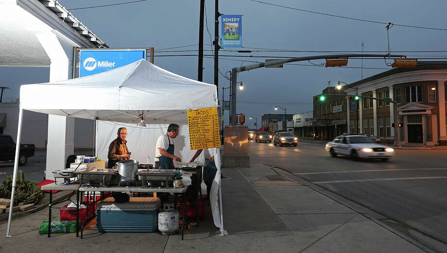 "Martin Herrera, 49, center in apron, sets up his taco stand at the corner of 2nd Street and West Main in Kenedy, Texas, Thursday, Feb. 7, 2013. Most every morning of the week, Herrera, of San Antonio, arrives at 4 a.m. to sell his tacos. On a good Friday, he'll sell up to 500 tacos to workers in the Eagle Ford Shale play. ""I follow the money. I started coming down in May,"" said Herrera. Next to Herrera is helper, Paul Longoria, 66, of Kenedy. Photo: Jerry Lara, San Antonio Express-News / ©2013 San Antonio Express-News"