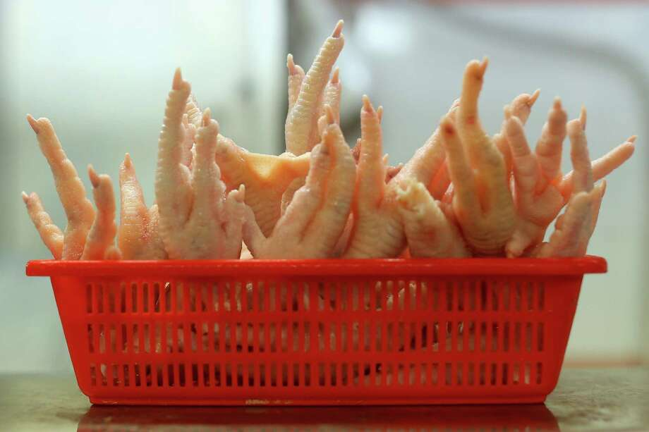 The Singapore Chinatown Complex Wet Market has pretty much anything you want to eat and perhaps some things you don't. These are chicken feet on display, Thursday, Feb. 21. 2013. The Chinatown Complex Wet Market is a traditional Asian food market popular with elder Singaporeans that features fresh seafood, meat, vegetables, Chinese groceries and a variety of exotic delicacies. The bustling complex floors are never dry with melting ice and water used to clean the floors, fish and vegetables spilling through the space, thus earning the name 'Wet Market'. The markets have retained their relevance by guaranteeing freshness and a personal service between stall mongers and loyal customers. Photo: Cameron Spencer, Getty / 2013 Getty Images