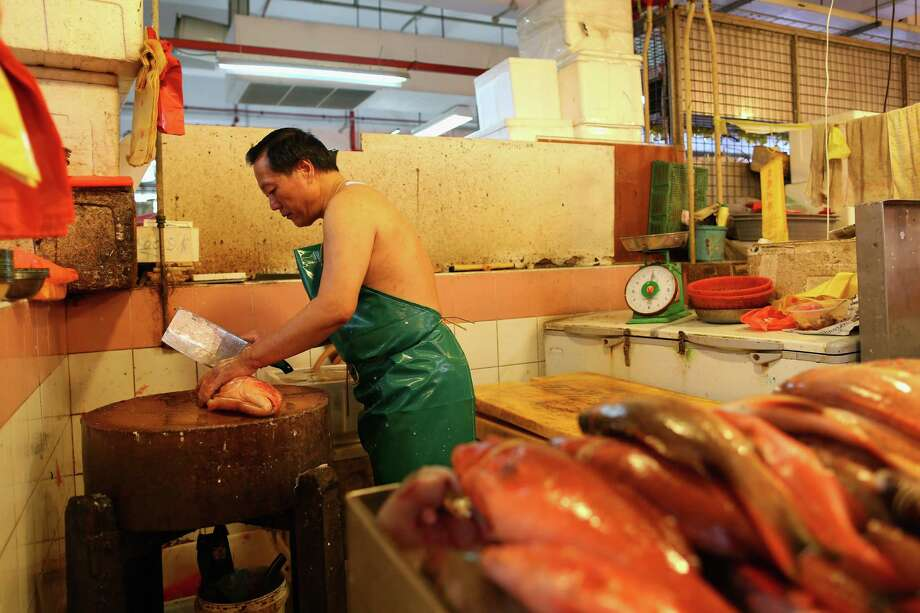 The Wet Market hums with activity. Here a fish monger producers fillets.  Photo: Cameron Spencer, Getty / 2013 Getty Images