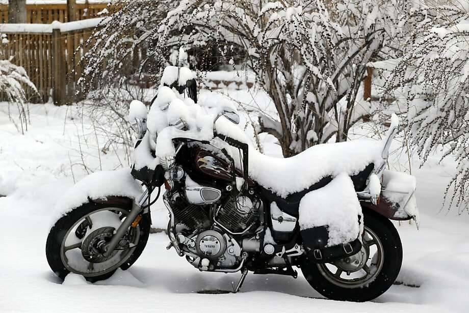 A motorcycle is covered in snow on a residential street in Denver on Thursday, Feb. 21, 2013. A fast moving winter storm passed through Colorado Wednesday night and Thursday morning dropping as much as a foot of snow in areas of the state. (AP Photo/Ed Andrieski) Photo: Ed Andrieski, Associated Press