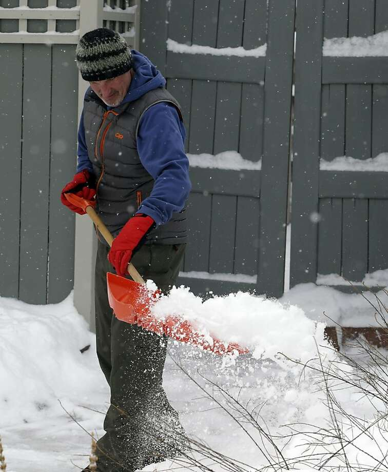 Kyle Kovalik shoves snow from his walk in Denver on Thursday, Feb. 21, 2013. A fast moving winter storm passed through Colorado Wednesday night and Thursday morning dropping as much as a foot of snow in areas of the state. (AP Photo/Ed Andrieski) Photo: Ed Andrieski, Associated Press