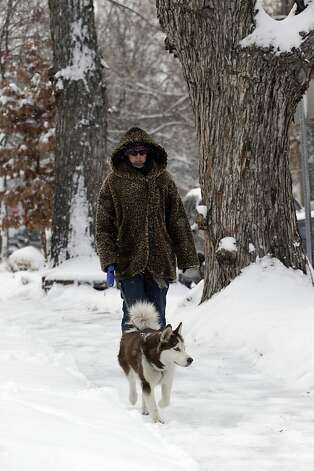 Lia Cervantes walks her dog Ruby in the snow in Denver on Thursday, Feb. 21, 2013. A fast moving winter storm passed through Colorado Wednesday night and Thursday morning dropping as much as a foot of snow in areas of the state. (AP Photo/Ed Andrieski) Photo: Ed Andrieski, Associated Press