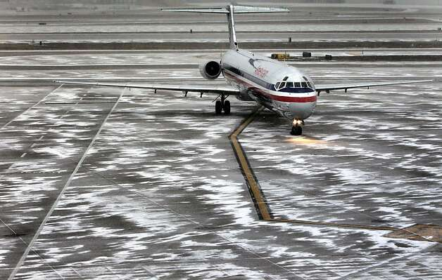 An American Airlines flight arrives as sleet falls at Lambert-St. Louis International Airport, on Thursday, Feb. 21, 2013. Blinding snow, at times accompanied by thunder and lightning, bombarded much of the nation's midsection Thursday. Freezing rain and sleet were forecast for southern Missouri, southern Illinois and Arkansas. St. Louis was expected to get all of the above — a treacherous mix of snow, sleet and freezing rain. (AP Photo/St. Louis Post-Dispatch, Robert Cohen)  EDWARDSVILLE INTELLIGENCER OUT; THE ALTON TELEGRAPH OUT Photo: Robert Cohen, Associated Press