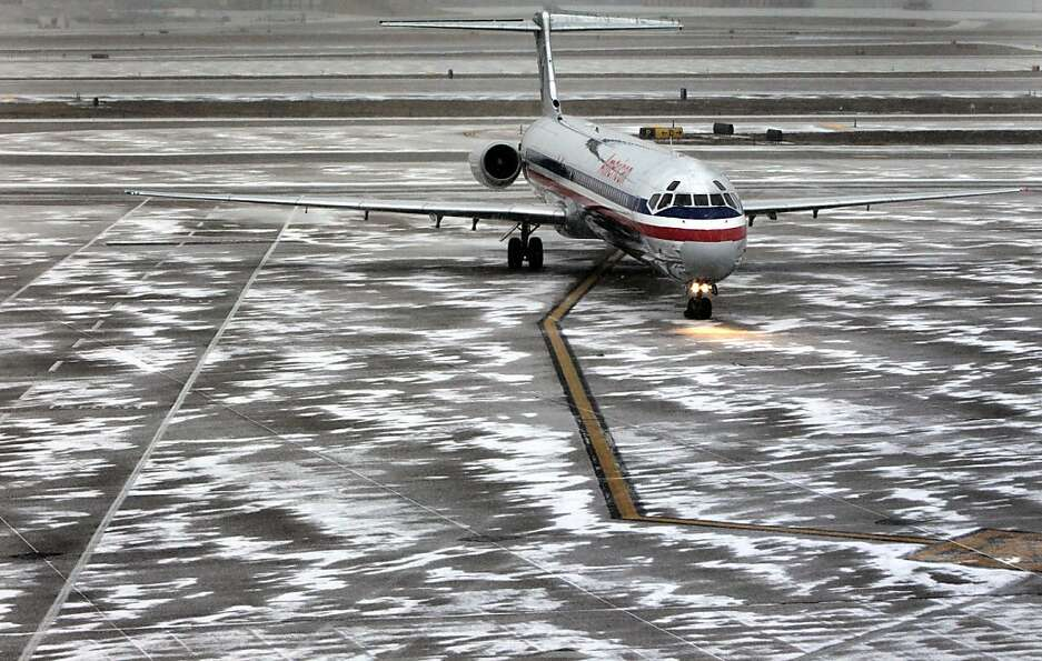 An American Airlines flight arrives as sleet falls at Lambert-St. Louis International Airport, on Th