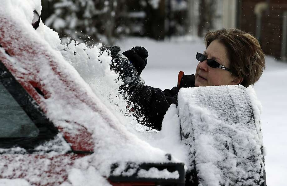 Kay Nelson scrapes ice and snow from her vehicle in Denver on Thursday, Feb. 21, 2013. A fast moving winter storm passed through Colorado Wednesday night and Thursday morning dropping as much as a foot of snow in areas of the state. (AP Photo/Ed Andrieski) Photo: Ed Andrieski, Associated Press