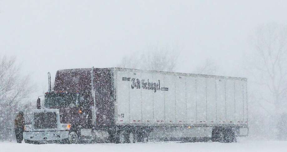 A trucker stops in almost whiteout conditions along K-10 highway near Eudora, Kan., Thursday, Feb. 21, 2013.  The Kansas Turnpike Authority encouraged drivers to stay off the turnpike entirely; it runs from Oklahoma to Kansas City. There was virtually zero visibility on the turnpike early Thursday. And I-70 and other major highways in Kansas were snowpacked and icy, according to the Kansas Department of Transportation. Kansas Gov. Sam Brownback closed executive offices, except for essential personnel. He urged residents to have an extra cup of coffee, get out a board game and play with their children. (AP Photo/Orlin Wagner) Photo: Orlin Wagner, Associated Press
