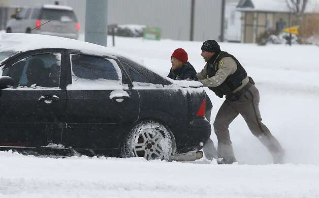 A Sedgwick County Sheriff's deputy helps a stranded motorist in Wichita, Kans. Thursday, Feb 21, 2013, as nearly a foot of snow covered the area. Kansas was the epicenter of the winter storm, with parts of Wichita buried under 13 inches of still-falling snow, but winter storm warnings stretched eastern Colorado through Illinois. (AP Photo/The Wichita Eagle, Bo Rader) Photo: Bo Rader, Associated Press
