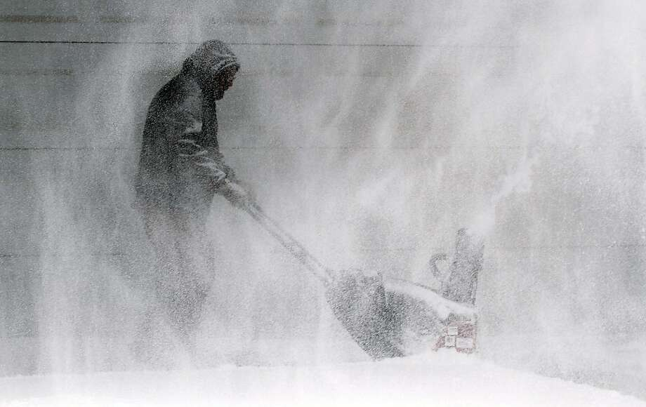 Tom McReynolds clears snow from a neigbors' house in Wichita, Kans.,Thursday, Feb. 21, 2013. Kansas was the epicenter of the winter storm, with parts of Wichita buried under 13 inches of still-falling snow, but winter storm warnings stretched eastern Colorado through Illinois. (AP Photo/The Wichita Eagle, Jaime Greene) Photo: Jaime Greene, Associated Press