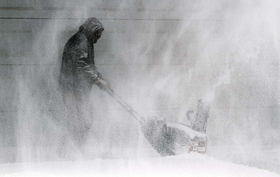 Tom McReynolds clears snow from a neigbors' house in Wichita, Kans.,Thursday, Feb. 21, 2013. Kansas