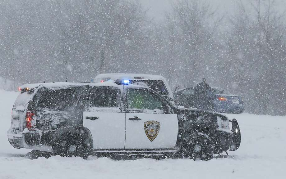 A Lenexa Police vehicle stops to aid motorists stuck on a ramp to I-35 in Lenexa, Kan., Thursday, Feb. 21, 2013. The Kansas Turnpike Authority encouraged drivers to stay off the turnpike entirely; it runs from Oklahoma to Kansas City. There was virtually zero visibility on the turnpike early Thursday. And I-70 and other major highways in Kansas were snowpacked and icy, according to the Kansas Department of Transportation. Kansas Gov. Sam Brownback closed executive offices, except for essential personnel. He urged residents to have an extra cup of coffee, get out a board game and play with their children. (AP Photo/Orlin Wagner) Photo: Orlin Wagner, Associated Press