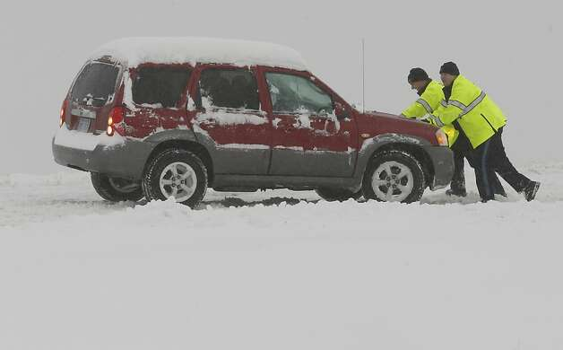 Motorist attempt to push a car back on the road in Wichita, Kans. Thursday, Feb 21, 2013.  Numerous cars and trucks were stuck or off the road as nearly a foot of snow fell across the area. Kansas was the epicenter of the winter storm, with parts of Wichita buried under 13 inches of still-falling snow, but winter storm warnings stretched eastern Colorado through Illinois. (AP Photo/The Wichita Eagle, Bo Rader) Photo: Bo Rader, Associated Press