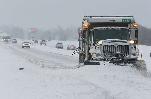 A city snow plow pusheds snow off of Zoo Blvd Thursday morning, Feb. 21, 2013 in Wichita, Kans. Kansas was the epicenter of the winter storm, with parts of Wichita buried under 13 inches of still-falling snow, but winter storm warnings stretched eastern Colorado through Illinois. (AP Photo/The Wichita Eagle, Bo Rader) Photo: Bo Rader, Associated Press
