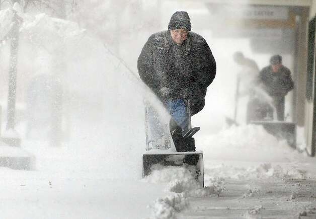 Chuck Carroll, center, uses a snow blower to clear the sidewalk in front of his business in downtown Salina, Kan. Thursday morning Feb. 21, 2013. Carroll said he had cleared the sidewalk Wednesday night and expected to remove snow at least once more Thursday. (AP Photo/Salina Journal, Tom Dorsey) Photo: Tom Dorsey, Associated Press