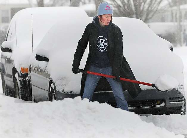 "Gina Pucket shovels snow from her driveway in Salina, Kan. Thursday morning, Feb. 21, 2013. Pucket said ""This is pretty easy, it's not heavy or wet, and it's not blowing."" (AP Photo/Salina Journal, Tom Dorsey) Photo: Tom Dorsey, Associated Press"