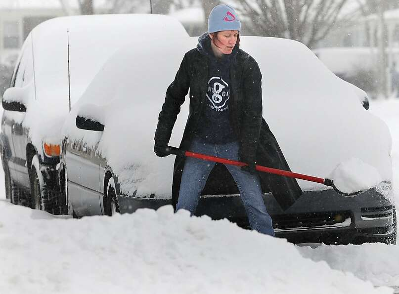 Gina Pucket shovels snow from her driveway in Salina, Kan. Thursday morning, Feb. 21, 2013. Pucket s