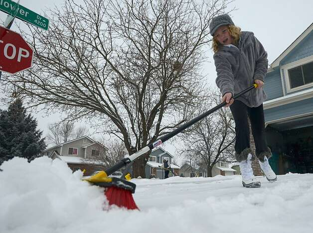 Delaney Schorr, 9, of Fort Collins, uses a push broom to remove snow from her driveway Thursday Feb. 21, 2013, where an over-night storm dropped about two inches on Fort Collins, Colo. Winter storm warnings were issued from eastern Colorado through Illinois. More than a foot of snow was expected in some places; a slippery mix of snow, sleet and freezing rain in others. Schools cancelled classes, sporting events had to reschedule and even lawmakers were staying home. Hundreds of flights were canceled.   (AP Photo/The Coloradoan, V. Richard Haro) Photo: V. Richard Haro, Associated Press