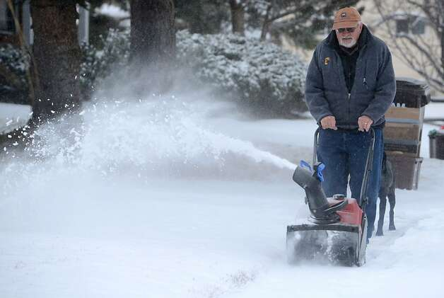 John Potyondy of Fort Collins, Colo. uses his snow blower to remove snow from his side walk Thursday Feb. 21, 2013, where an over-night storm dropped about two inches on Fort Collins.  Winter storm warnings were issued from eastern Colorado through Illinois. More than a foot of snow was expected in some places; a slippery mix of snow, sleet and freezing rain in others. Schools cancelled classes, sporting events had to reschedule and even lawmakers were staying home. Hundreds of flights were canceled.  (AP Photo/The Coloradoan, V. Richard Haro) Photo: V. Richard Haro, Associated Press