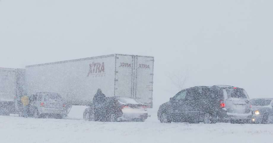 Drivers get out of their vehicles after a ramp is blocked by truck stuck in snow along I-35 in the Kansas City suburb of Overland Park, Kan., Thursday, Feb. 21, 2013.  The Kansas Turnpike Authority encouraged drivers to stay off the turnpike entirely; it runs from Oklahoma to Kansas City. There was virtually zero visibility on the turnpike early Thursday. And I-70 and other major highways in Kansas were snowpacked and icy, according to the Kansas Department of Transportation. Kansas Gov. Sam Brownback closed executive offices, except for essential personnel. He urged residents to have an extra cup of coffee, get out a board game and play with their children. (AP Photo/Orlin Wagner) Photo: Orlin Wagner, Associated Press