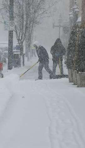 Workers clear the sidewalk on the Country Club Plaza shopping district in Kansas City, Mo., Thursday, Feb. 21, 2013.  The Missouri Department of Transportation said Interstate 44 near Springfield was completely covered with ice Thursday morning. Traffic was moving very slow and the DOT urged drivers to use extreme caution or stay home. St. Louis-area road crews were out in full force early Thursday, even though it was dry. The region was expecting a volatile mix of snow, sleet, ice and freezing rain by midday and crews were hoping to lay down enough salt to keep at least the major roadways moving. (AP Photo/Orlin Wagner) Photo: Orlin Wagner, Associated Press