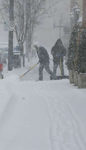 Workers clear the sidewalk on the Country Club Plaza shopping district in Kansas City, Mo., Thursday