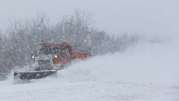 A plow tries to clear K-10 highway near DeSoto, Kan., Thursday, Feb. 21, 2013. The Kansas Turnpike Authority encouraged drivers to stay off the turnpike entirely; it runs from Oklahoma to Kansas City. There was virtually zero visibility on the turnpike early Thursday. And I-70 and other major highways in Kansas were snowpacked and icy, according to the Kansas Department of Transportation. Kansas Gov. Sam Brownback closed executive offices, except for essential personnel. He urged residents to have an extra cup of coffee, get out a board game and play with their children. (AP Photo/Orlin Wagner) Photo: Orlin Wagner, Associated Press