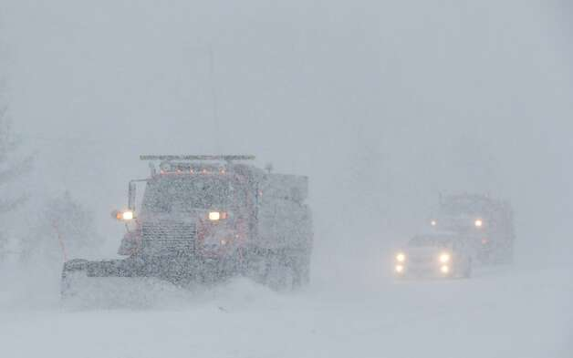 Plows try to clear Shawnee Mission Parkway in the Kansas City suburb of Shawnee Mission, Kan., Thursday, Feb. 21, 2013.  The Kansas Turnpike Authority encouraged drivers to stay off the turnpike entirely; it runs from Oklahoma to Kansas City. There was virtually zero visibility on the turnpike early Thursday. And I-70 and other major highways in Kansas were snowpacked and icy, according to the Kansas Department of Transportation. Kansas Gov. Sam Brownback closed executive offices, except for essential personnel. He urged residents to have an extra cup of coffee, get out a board game and play with their children. (AP Photo/Orlin Wagner) Photo: Orlin Wagner, Associated Press