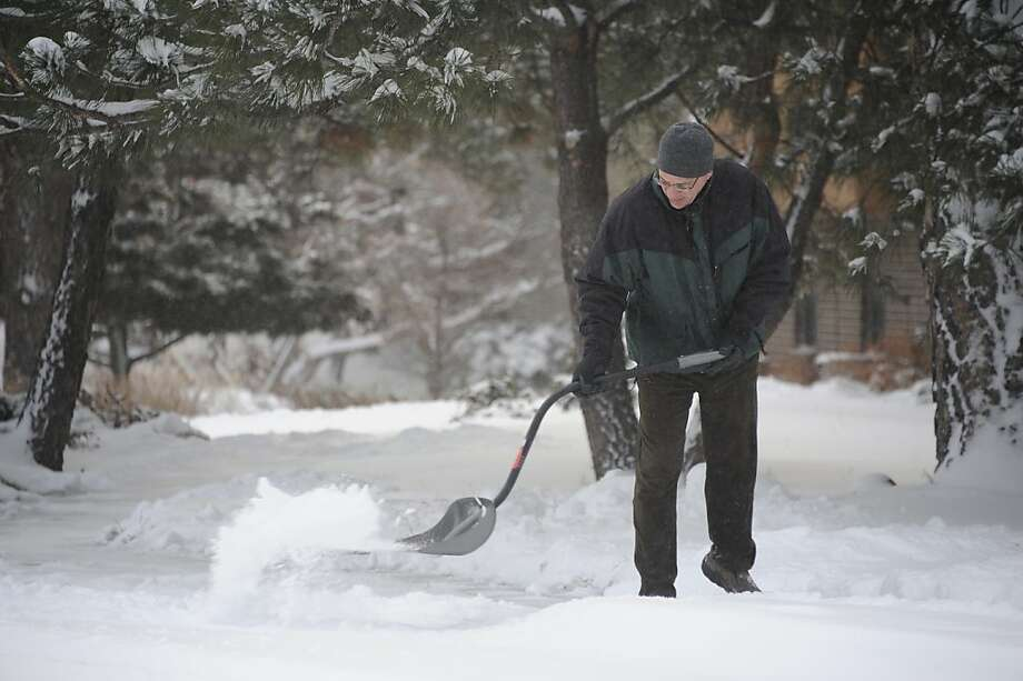 Keith Houin shovels his sidewalk in Springs Colo. following an overnight snowstorm Thursday, Feb. 21, 2013.  Winter storm warnings were issued from eastern Colorado through Illinois Thursday. (AP Photo/The Colorado Springs Gazette, Mark Reis)    NO MAGS NO SALES Photo: Mark Reis, Associated Press