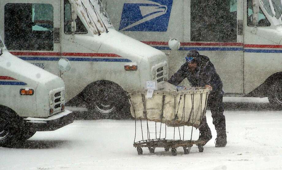 U.S. Postal Service employee Craig Conner tries to navigate a mail cart to his vehicle Thursday morning Feb. 21, 2013 in downtown St. Joseph, Mo., shortly after the snow storm started. Winter storm warnings were issued from eastern Colorado through Illinois Thursday. (AP Photo/St. Joseph News-Press, Todd Weddle) Photo: Todd Weddle, Associated Press