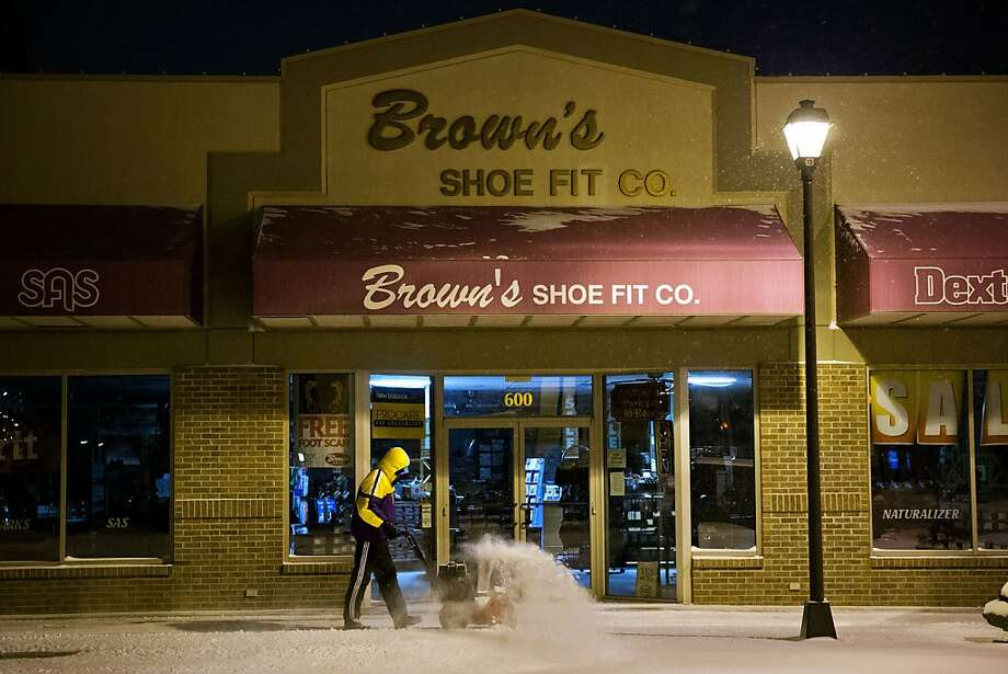 Denoy Smith, manager of Brown's Shoe Fit Co.  removes snow from the store's sidewalk Thursday Feb. 21, 2013, in Hastings Neb.  Winter storm warnings were issued from eastern Colorado through Illinois Thursday. (AP Photo/ The Omaha World-Herald/Ryan Soderlin) MAGS OUT TV OUT Photo: Ryan Soderlin, Associated Press