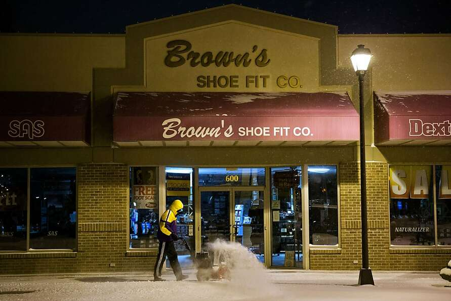 Denoy Smith, manager of Brown's Shoe Fit Co.  removes snow from the store's sidewalk Thursday Feb. 2