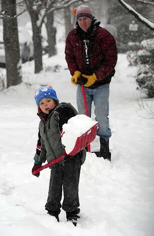 Levi Mushovic, 4, helps his dad Brad clean their neighborhood sidewalk in Boulder, Colo on a snowy Thursday morning, Feb. 21, 2013. (AP Photo/The Daily Camera, Paul Aiken) NO SALES Photo: Paul Aiken, Associated Press