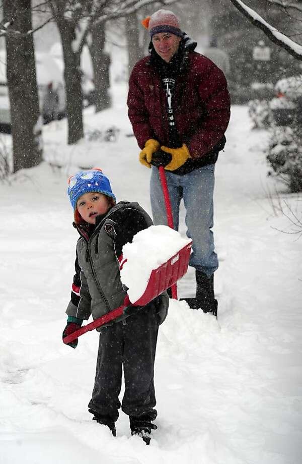 Levi Mushovic, 4, helps his dad Brad clean their neighborhood sidewalk in Boulder, Colo on a snowy Thursday morning, Feb. 21, 2013. (AP Photo/The Daily Camera, Paul Aiken) NO SALES Photo: Paul Aiken, Associated Press
