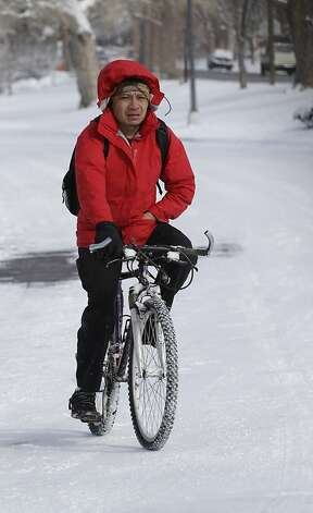 Hector Valdez rides his bike through the snow in Denver on Thursday, Feb. 21, 2013. A fast moving winter storm passed through Colorado Wednesday night and Thursday morning dropping as much as a foot of snow in areas of the state. (AP Photo/Ed Andrieski) Photo: Ed Andrieski, Associated Press
